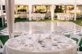 White reception tent with tables covered in white tablecloths surrounded by white chairs