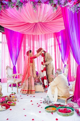 pink and purple hindu wedding ceremony, bride places flower garland around groom's neck