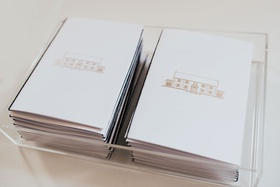 wedding ceremony program with gold drawing of venue in acrylic lucite clear box