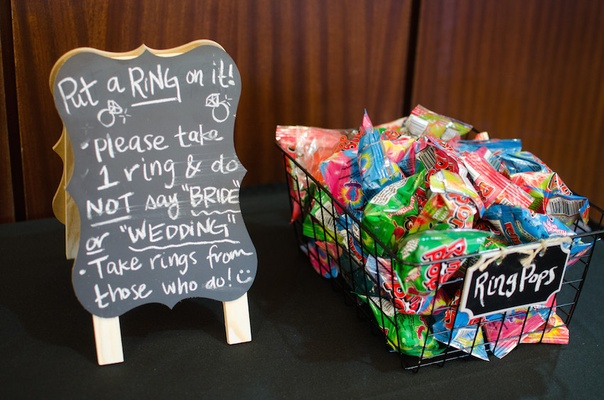 Ring pop candies in a basket next to chalkboard with rules of game for a bridal shower