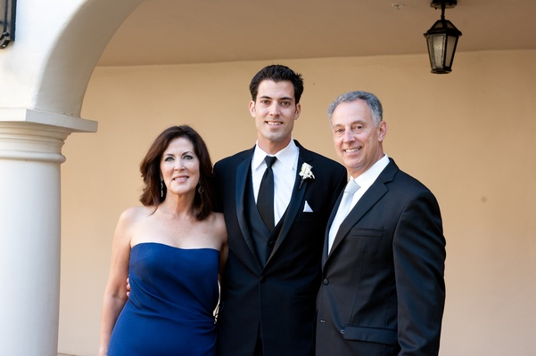 Groom and father with mother of bride in strapless gown