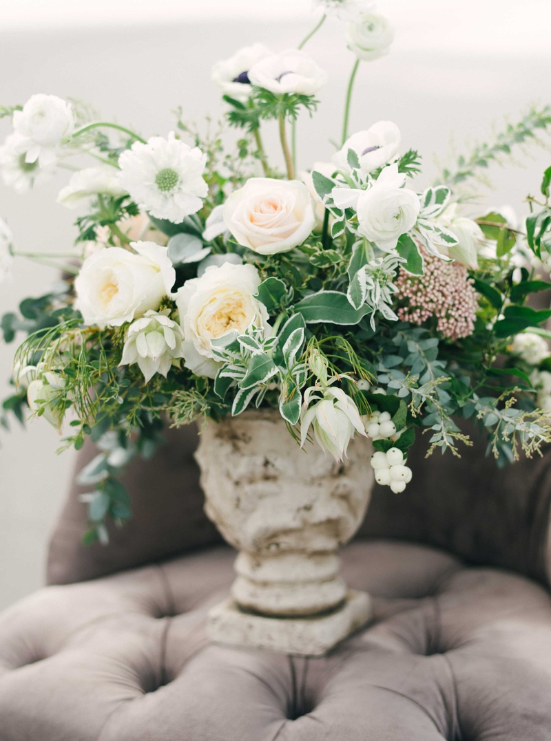 lush floral arrangement with white and blush flowers and lots of green leaves on tufted grey chair