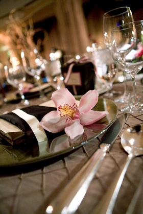 pink orchid rests on place next to brown napkin