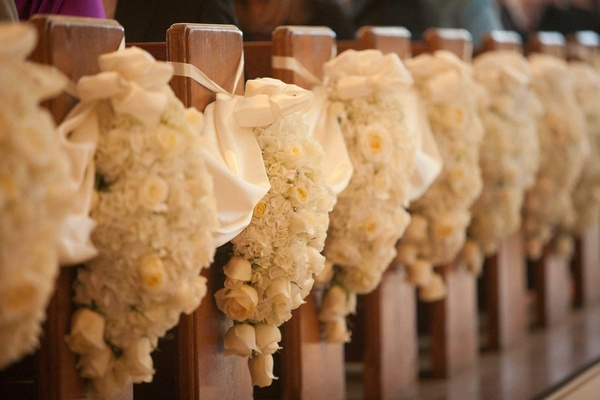 Pews decorated with arrangements of white flowers for a wedding
