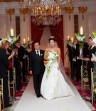 Bride walks down aisle at ballroom wedding