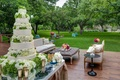 Wedding reception with white wedding cake surrounded by green trees on a ranch in Texas