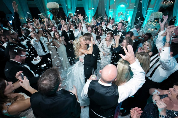 Bride in a strapless Ines Di Santo wedding dress kisses groom in black tuxedo, surrounded by guests