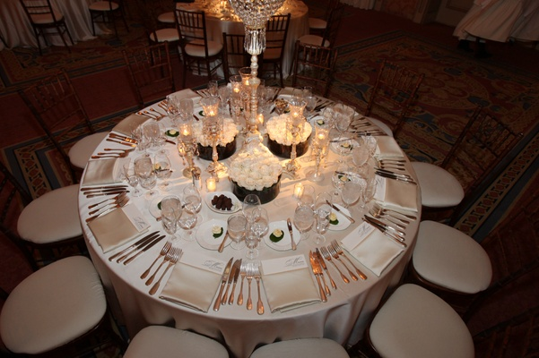 Reception table with white tablecloth, candles in crystal holders, and arrangements of white roses