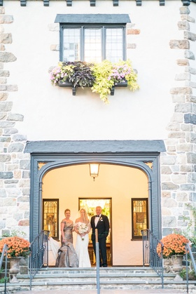 Wedding ceremony bride entrance with mother and father parents doorway to chateau venue
