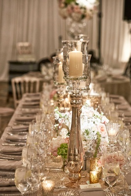 Wedding reception long table with runner, gold candle votive, and white pink flowers