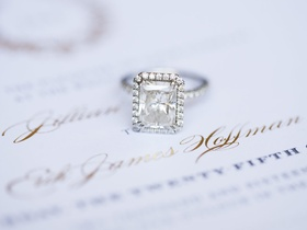 Diamond engagement ring with emerald cut diamond and halo pave band