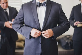Groom buttoning suit jacket with black bow tie