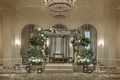 grey wooden chuppah with accents of greenery at indoor wedding