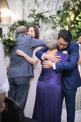 bride hugging father and groom hugging mother at ceremony