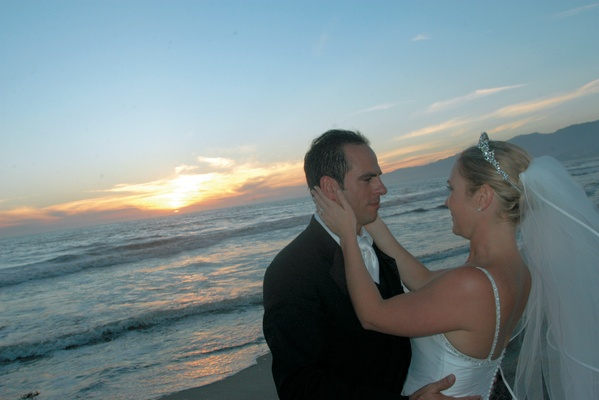 newlyweds gaze at each other on beach