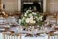 Gold chairs around white table with gold fotted vase with roses and white flowers greenery candles