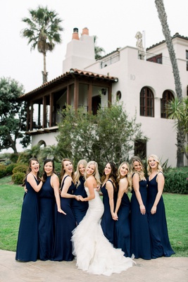 bride in strapless mermaid wedding dress with bridesmaids in navy blue dresses mismatch necklines