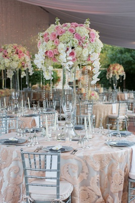 Wedding reception with tall flower arrangement pink white blooms orchids crystals silver chairs