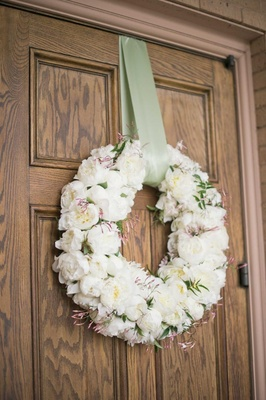White peony wreath with green ribbon on church door