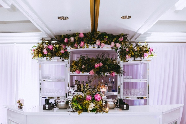 Wedding after party fresh flowers pink peony greenery decorating all white bar at after party drapes