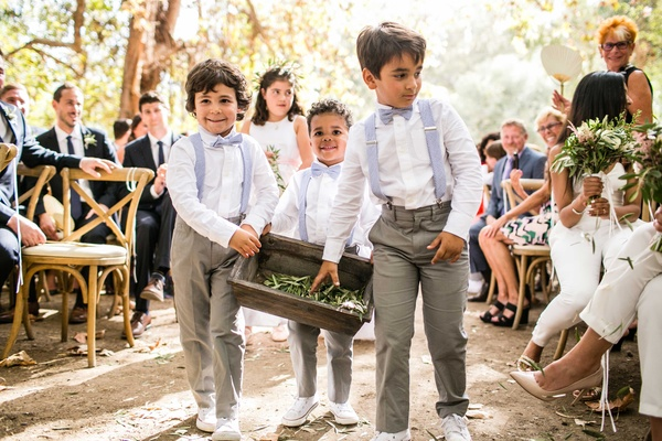 Boy ring bearers in grey pants and blue suspenders and bow ties tossing olive sprig leaves on aisle