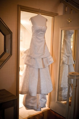 Tiered Carolina Herrera wedding dress on hanger