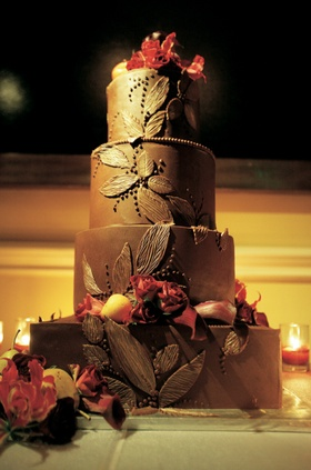 Four layer cake with red roses and brown frosting