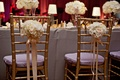 Gold chairs with purple cushions and ivory arrangements