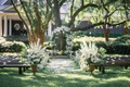 outdoor plantation-like wedding, white flowers, greenery, benches
