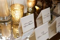 Black and white tent escort cards on mirrored table net to gold candle votives and hurricanes