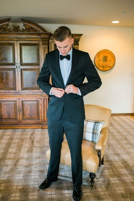 groom buttons coat jacket of tuxedo preparing for wedding ceremony