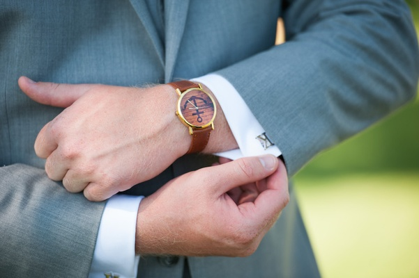 Groom in grey suit, watch with brown leather band, anchor graphic on dial, silver letter K cuff link