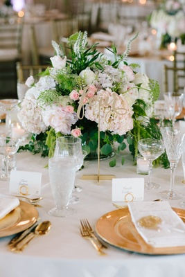 White wedding reception table linen, gold charger plate, green and white centerpiece, pink rosebuds