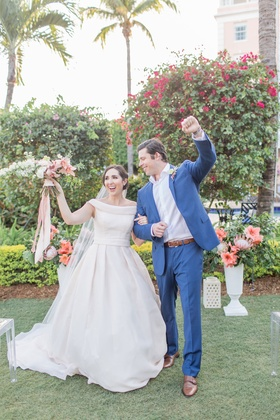 The Confused Millennial off shoulder wedding dress after ceremony bouquet groom's arm in air navy