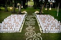White chair covers on ceremony lawn with flower petal aisle