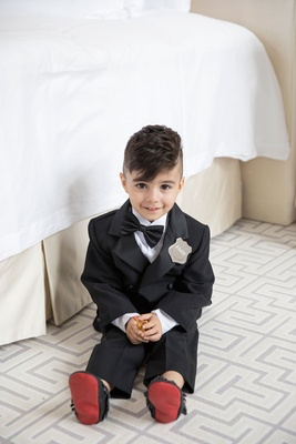 Ring bearer with cute haircut bow tie silver badge red bottom moccasins tuxedo mini on floor