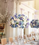 tall weddign reception centerpiece with blue, purple, pink, and white flowers