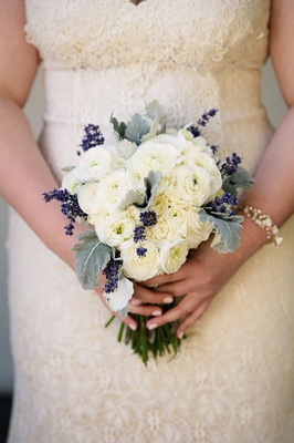 Bride in lace wedding dress holding bouquet with dusty miller lamb's ear, ranunculus flowers purple