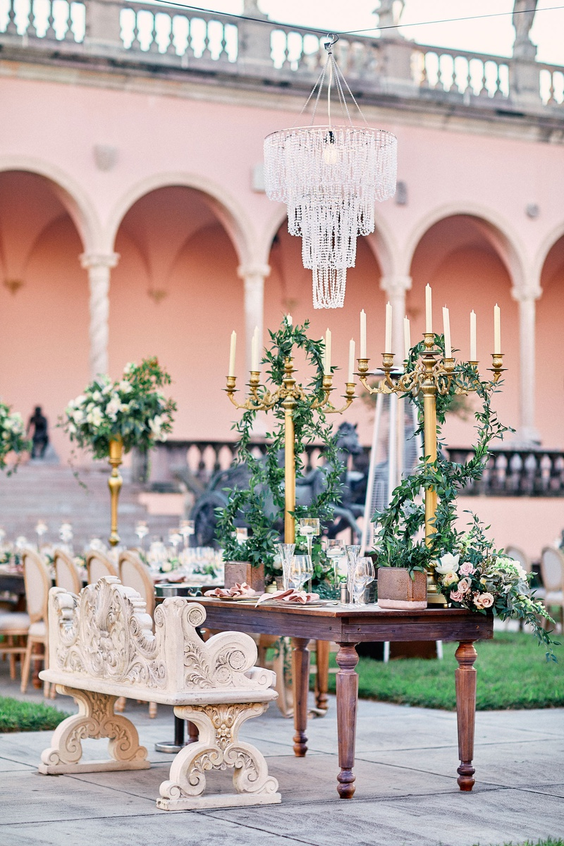 chandelier suspended over opulent, ornate sweetheart table with carved bench