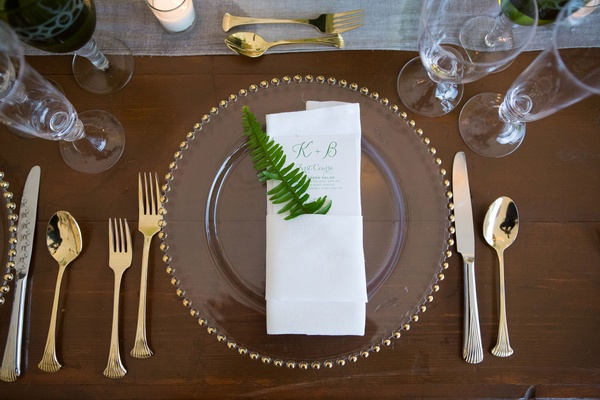 Gold flatware fork knife spoon gold beaded charger plate with menu napkin and fern decoration green