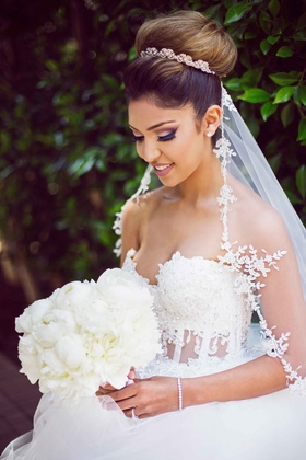 bride smiling bouquet bold makeup eye shadow wedding look big bun up-do white bouquet