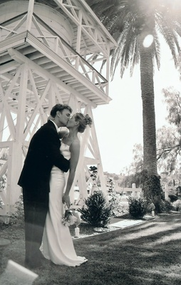 Black and white photo of couple kissing under palm tree