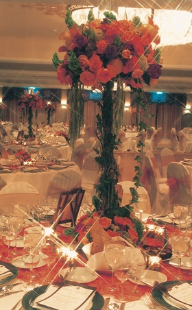 table with orange tablecloth and centerpiece with green base and orange flowers