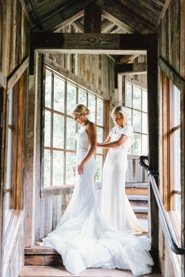 The mother of the bride in white short sleeve dress helping bride into inbal dror gown