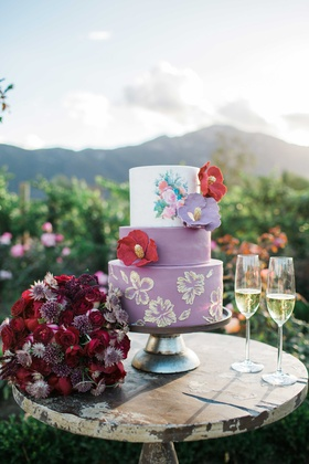 purple red pink wedding cake sugar floral detailing with gold on rustic table on vineyard dessert