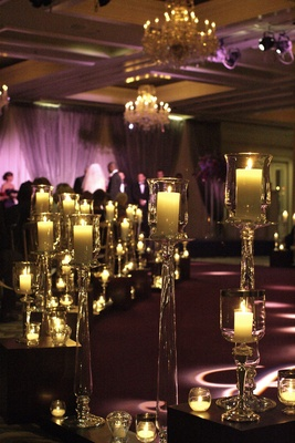 Wedding ceremony in a ballroom with purple lighting and lots of candles in crystal containers