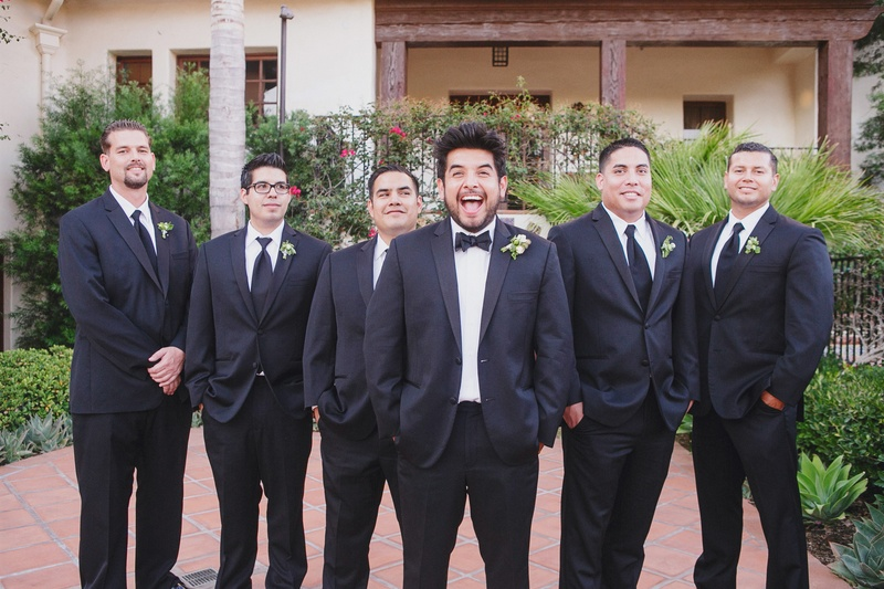 Excited groom in bow tie with groomsmen in suits