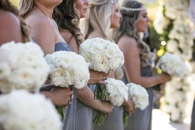 bridesmaids in grey blue periwinkle dresses strapless holding white bouquets in line processional