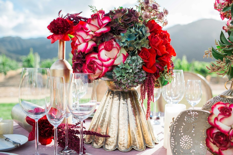 red and white flower floral arrangement in gold vase pink table linen vineyard