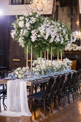 long wooden table with sheer white fabric runner and white and green centerpiece on gold stand